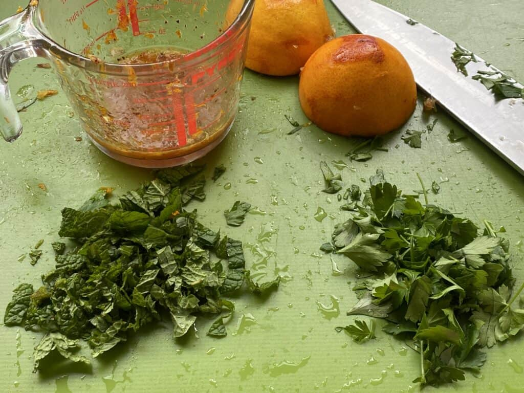 Chopped Herbs and a jug of  Salad Dressing on a green chopping board.