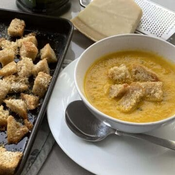 Baked croutons on a baking tray with a bowl of soup