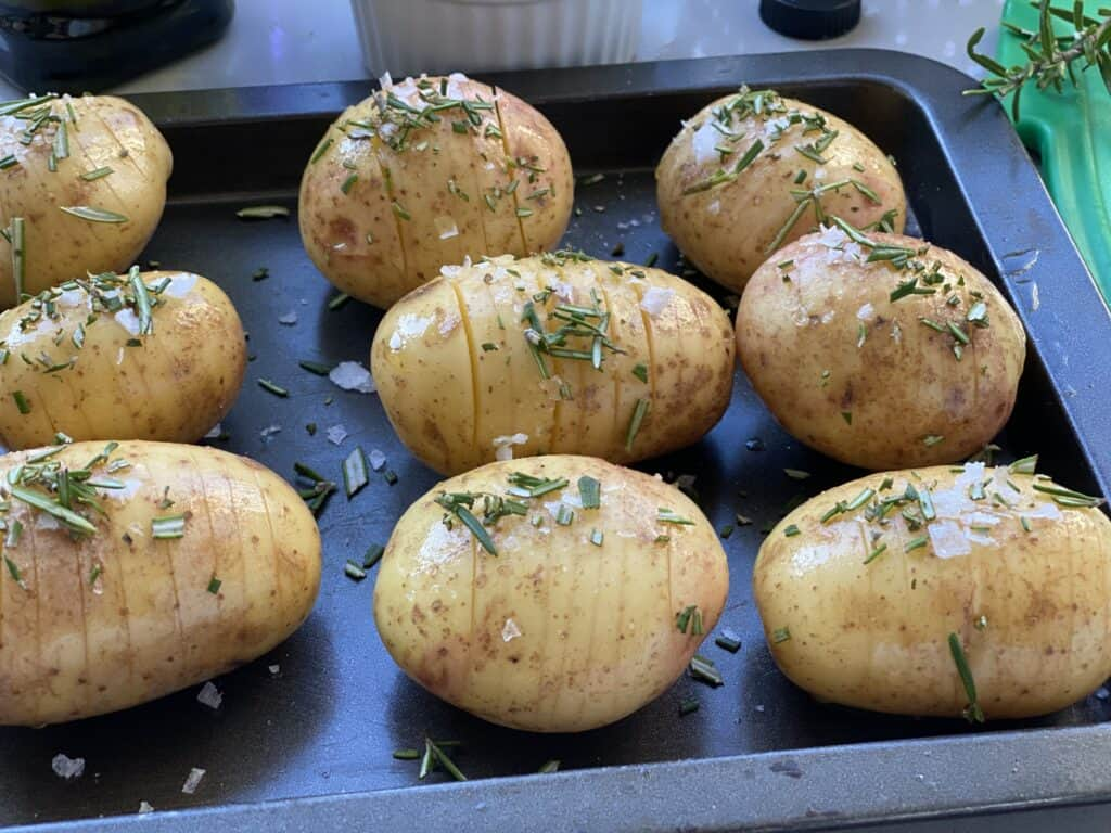 Hasselback potatoes sprinkled with salt and rosemary ready to bake
