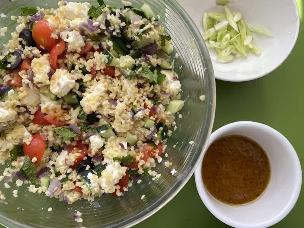 Overhead shot of Bulgar Salad and bowl of dressing