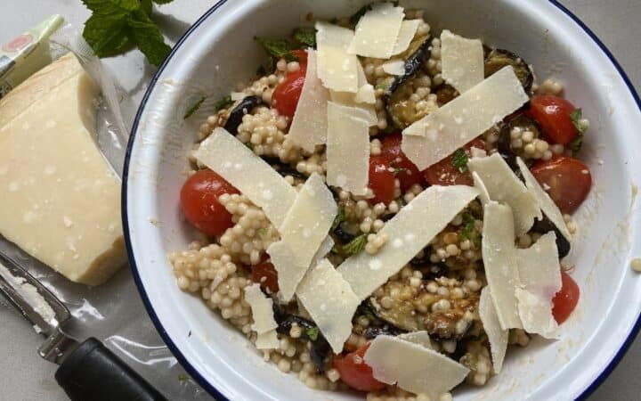 Overheat shot of Aubergine, Tomato and Couscous Salad in a white dish